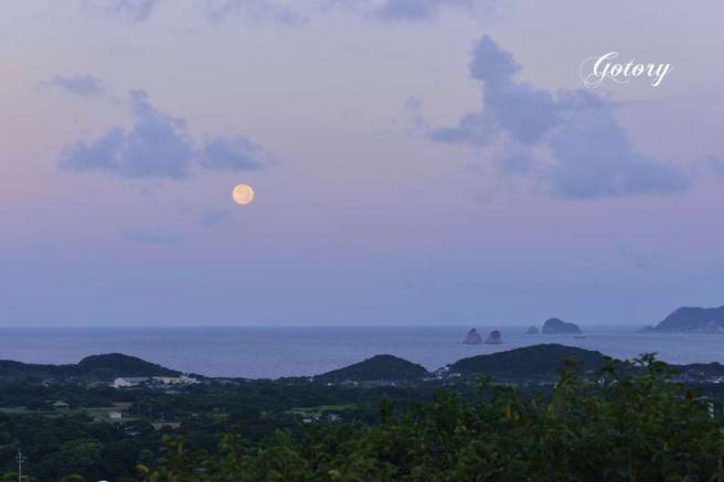 西の海に沈む満月